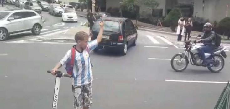 Criança controla o trânsito com apito e patinete