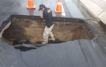 Chuvas: Asfalto cede e cratera se abre