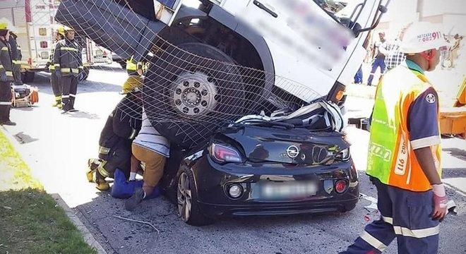 Mulher tem carro esmagado por caminhão desgovernado, mas sobrevive