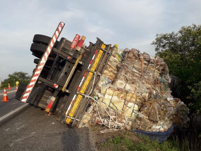 Caminhão carregado de plástico tomba em rodovia